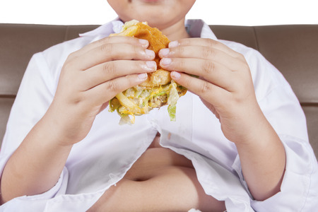 obesity kids: Close up of hands of little boy holding a cheeseburger with potbelly sitting on the sofa