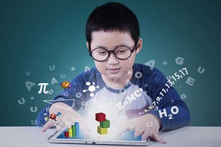 computer science: Portrait of a cute elementary school student using application on the tablet for studying Stock Photo