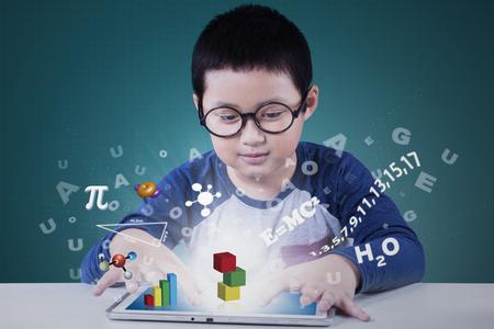 Portret van een schattig basisschool student met behulp van applicatie op de tablet voor het bestuderen