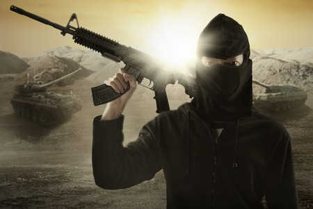 guerrilla warfare: Male terrorist wearing mask and holding a machine gun with military vehicle background