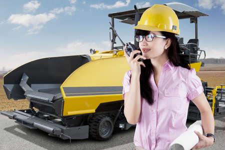 talkie: Female supervisor talking on the walkie talkie with asphalt machine on the road Stock Photo