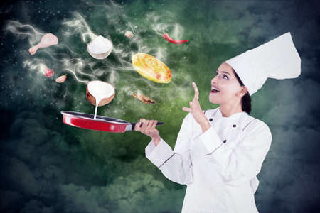 carne de pollo: Hermosa chef indio cocinar con magia en la sartén mientras se usan uniforme del cocinero Foto de archivo