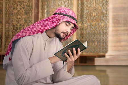 religious clothing: Portrait of a young middle eastern person sitting in the mosque while reading Quran