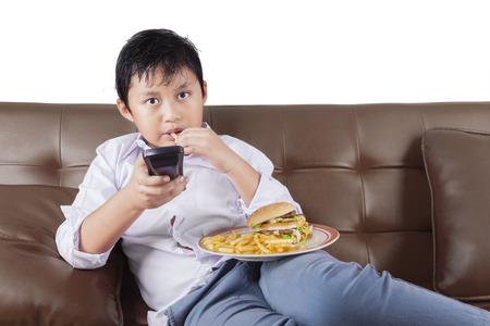 Portret van een schattige kleine jongen zittend op de bank tijdens het kijken naar tv en genieten van een plaat van fast food