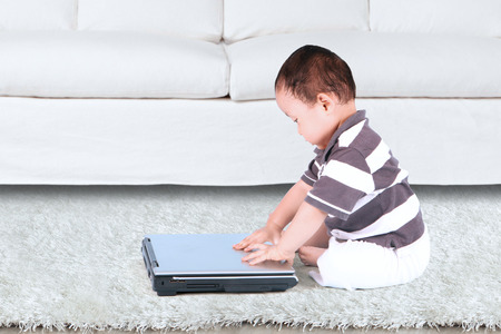 netbooks: Adorable baby holding a laptop and sitting near the sofa at home