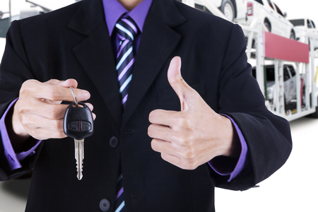 autotruck: Businessman hands showing a car key and thumb up with trailer truck background