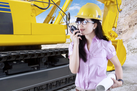 talkie: Portrait of female contractor talking on the walkie talkie with an excavator in the construction site