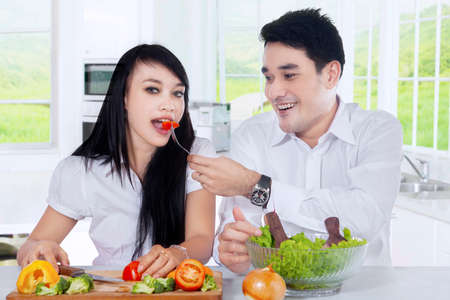 young wife: Young man feeding his wife with tomato while making vegetable salad together in the kitchen