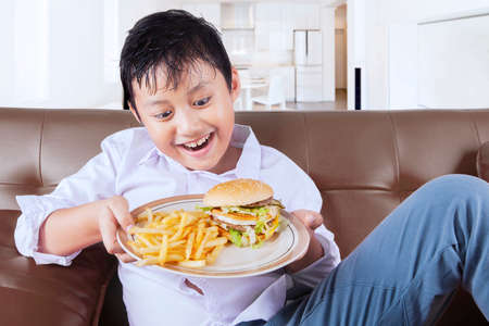 fat food: Portrait of a cute boy sitting on the sofa and ready to eat a plate of junk food at home Stock Photo
