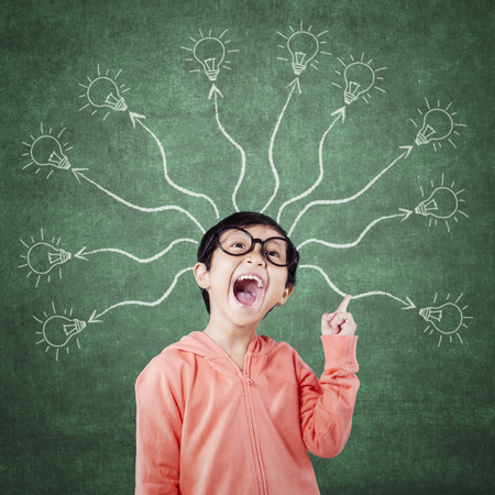 branching: Cheerful elementary school student standing in the class with branching light bulb. Concept of a branching mind Stock Photo