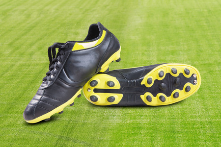soccer shoes: Pair of black soccer shoes. Shot in green grass field Stock Photo