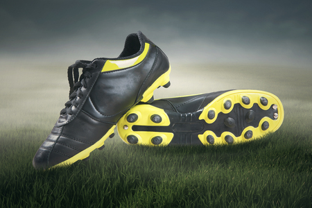 football shoes: Pair of football shoes on green grass and blue sky Stock Photo