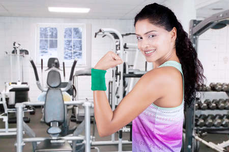 strong women: Portrait of pretty woman wearing sportswear and showing her bicep at gym, shot in winter season