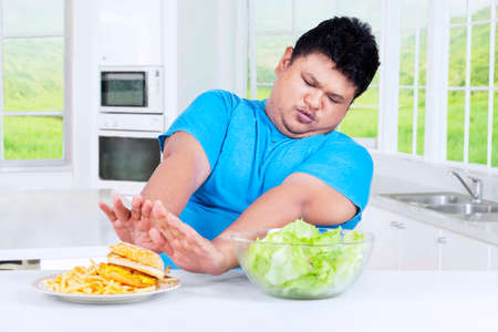 avoid: Picture of overweight person avoid a plate of junk food on the table in the kitchen at home