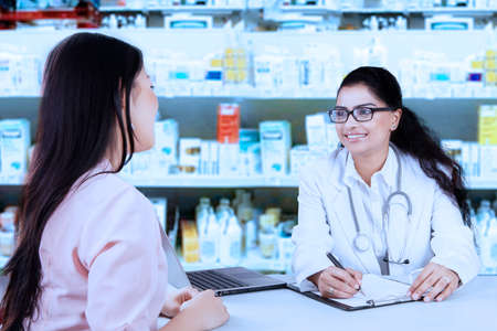 medicine cabinet: Portrait of young female doctor talking with patient and making a prescription, shot with medicine cabinet background
