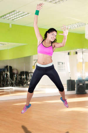 weight loss success: Joyful indian woman celebrate her weight loss success and jumping in the fitness center with sportswear