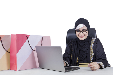 emoney: Portrait of arabian woman using a laptop and credit card for shopping online, isolated on white background