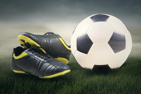 soccer shoes: Sport equipment concept of a ball and soccer shoes in football field under the sky