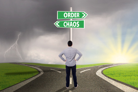 chaos order: Businessman standing on the road looking at signpost of order and chaos