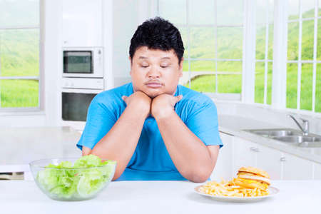 choose person: Portrait of confused overweight person to choose salad or burger, sitting in the kitchen at home Stock Photo