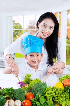 mama e hijo: Foto de la feliz madre y su hijo ensalada de verduras para cocinar juntos en la cocina Foto de archivo