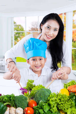 mom son: Photo of happy young mother and her son cooking vegetables salad together in the kitchen