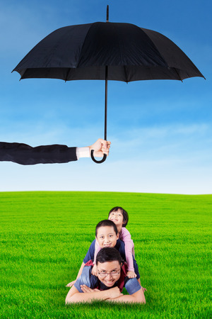 protection plan: Image of young father lying on the meadow with his children and smiling at the camera under umbrella