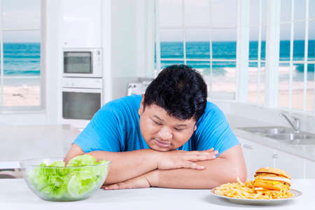 adult sandwich: Overweight man sitting in the kitchen while looking at a bowl of salad and looks confused Stock Photo