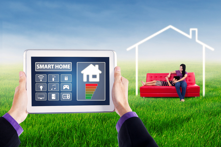temperature controller: Image of smart house controller applications on the digital tablet screen with young woman and her child sitting on sofa under a house symbol Stock Photo