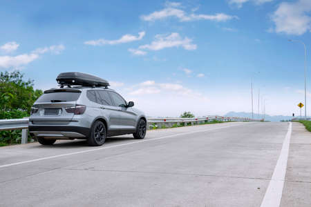 rack wheel: Image of a car is parked on the roadside while carrying roof rack for traveling