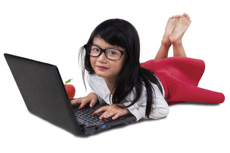asia children: Portrait of a beautiful little girl lying in the studio while using laptop computer, isolated on white background Stock Photo
