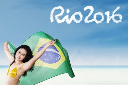 brazil beach swimsuit: Beautiful girl wearing bikini and holding a Brazilian flag on the beach with text of Rio 2016