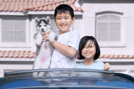 sunroof: Happy two children standing on the sunroof of the car while holding little siberian husky puppy and smiling at the camera