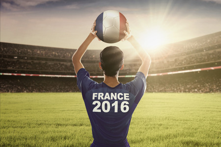costume ball: Picture of football player wearing costume of Euro 2016 France and ready to throw a ball in the stadium Editorial