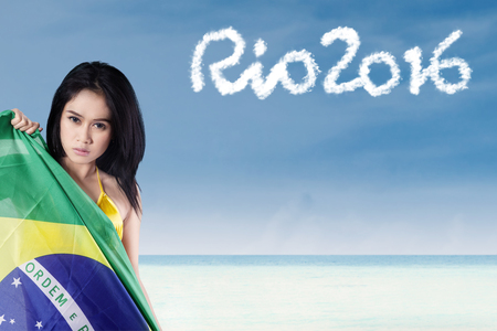 brazil beach swimsuit: Young woman holding national flag of brazil on the beach with text of Rio 2016