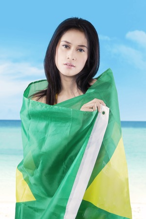 brazil beach swimsuit: Beautiful girl standing on the beach while covering her body with Brazilian flag Stock Photo