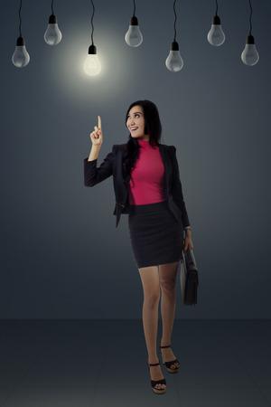 idea bulb: Creativity concept: beautiful businesswoman get a good idea while pointing a bright light bulb