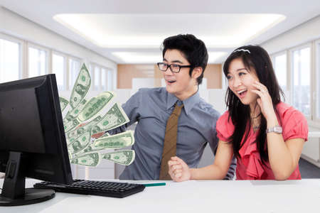 earn money: Portrait of two happy workers earn money online and look at the money on the monitor