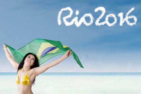 brazil beach swimsuit: Sexy woman wearing bikini and holding Brazilian flag on the beach with text of Rio 2016