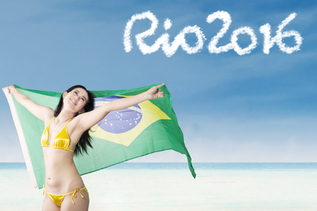 brazil beach swimsuit: Cheerful woman wearing bikini on the beach while holding a flag of Brazil with text of Rio 2016