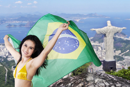 rio: Portrait of cheerful young girl wearing bikini while holding flag of Brazil with Rio de Janeiro city background Editorial