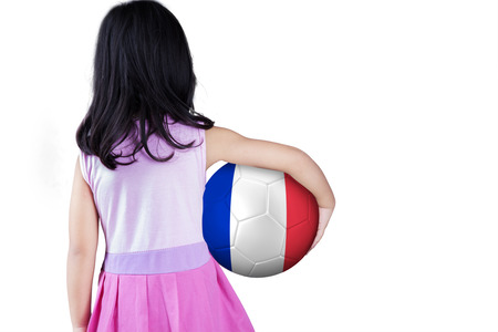 white back: Backside of little girl standing in the studio while holding a soccer ball with flag of France Stock Photo