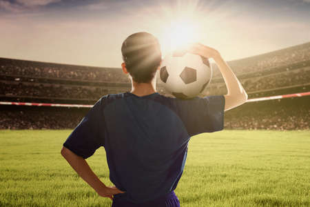 games hand: Backside of football player wearing blue uniform and holding a ball on his shoulder in the stadium Stock Photo