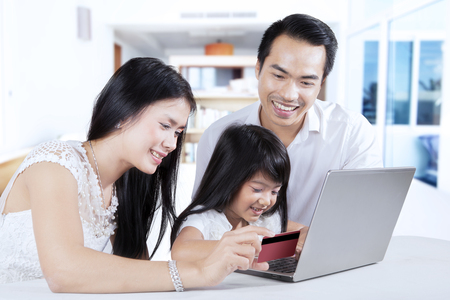 Portrait of happy family using laptop computer and credit card for shopping and paying online