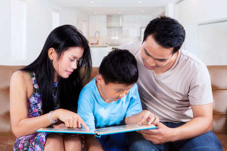 storybook: Photo of a little boy and his parents sitting on the sofa while reading a storybook together at home