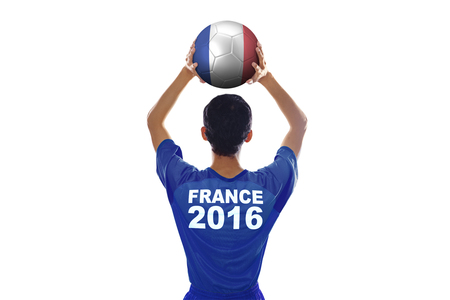 costume ball: Backside of football player of Euro 2016 France wearing soccer costume and lifting a ball in the studio
