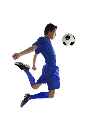 receives: Picture of football player wearing blue uniform and receives a ball with his chest while jumping in the studio