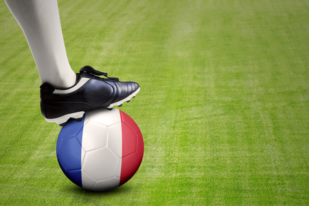 penalty flag: Close up of foot of football player and a ball with a France flag on the meadow.
