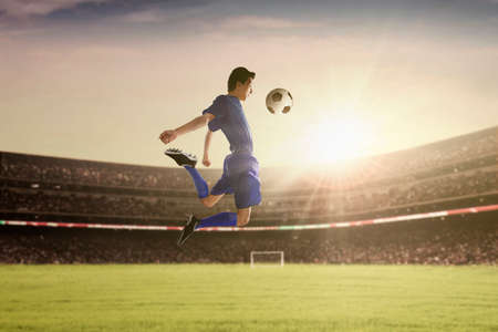 football play: Portrait of football player withstand a ball with his chest at the stadium