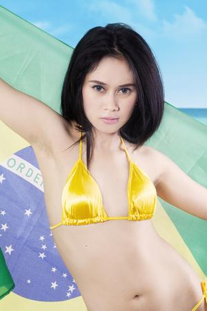 latina girl: Portrait of sexy female model wearing yellow swimwear while holding Brazilian flag at the coast